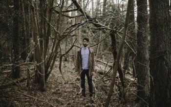 direct gaze,beard,forest,jacket,trees,branches