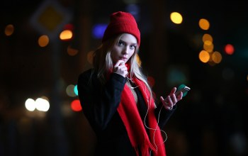 girl,blonde,looking at viewer,blue eyes,photo,long hair,depth of field,iphone,finger on lips,hood,lips,lights,black coat,scarf,looking at camera,mouth,straight hair,Face,portrait,coat,smartphone