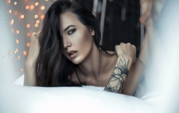 lying on front,hair in face,mouth,depth of field,gray eyes,bare shoulders,close up,long hair,lips,portrait,looking at camera,looking at viewer,open mouth,Face,photo,brunette,tattoo,girl