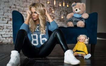puppets,Face,portrait,leather leggings,doll,tattoo,long hair,Roma Bakardi,Ekaterina Kolisnichenko,Couch,lips,blonde,Sneakers,sitting,on the floor,looking at camera,pants,depth of field,leather pants,looking at viewer,Teddy Bears,wavy hair,mouth,girl,juicy lips,photo