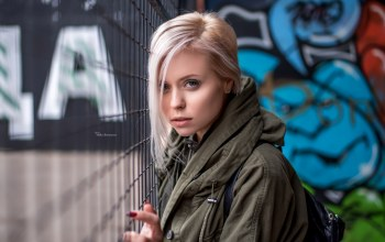 red nails,graffiti,blue eyes,depth of field,looking at viewer,Maxim Romanov,blonde,photographer,photo,lips,grey jacket,portrait,Face,close up,Maksim Romanov,jacket,girl,looking at camera,mouth